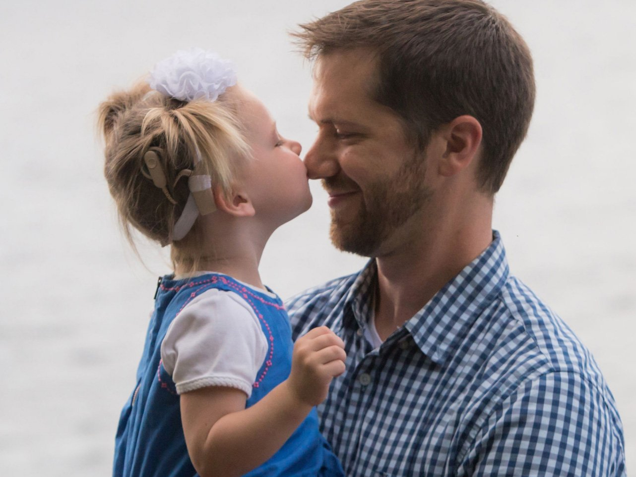 Little girl kissing father on the nose